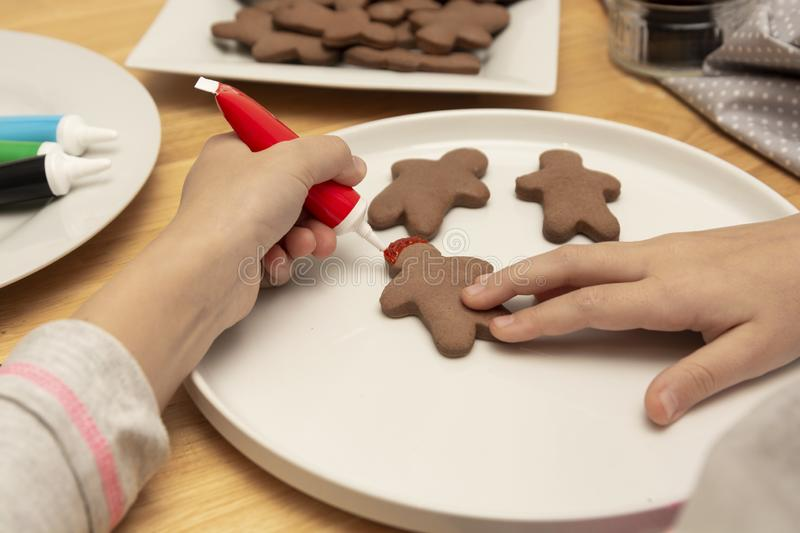 Child& x27;s hands decorating a christmas gingerbread cookies using colored glazeon, wooden table, top view. Christmas cookies royalty free stock photos