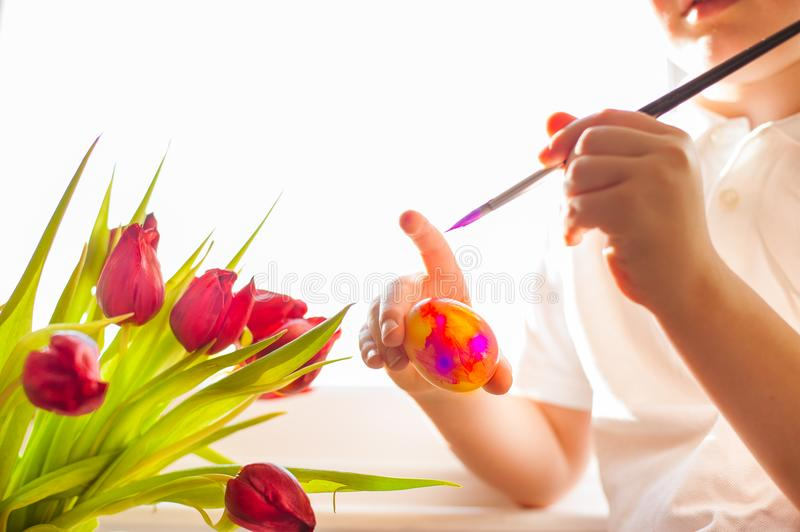 Child`s hands decorating Easter egg. Negative space. stock photos