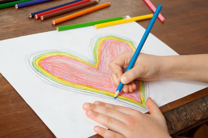 Child's Hands are Drawing a Heart That. Little Girl is Drawing Red Heart. Mothers Day. Fathers Day. Valentines Day. Birthday stock image