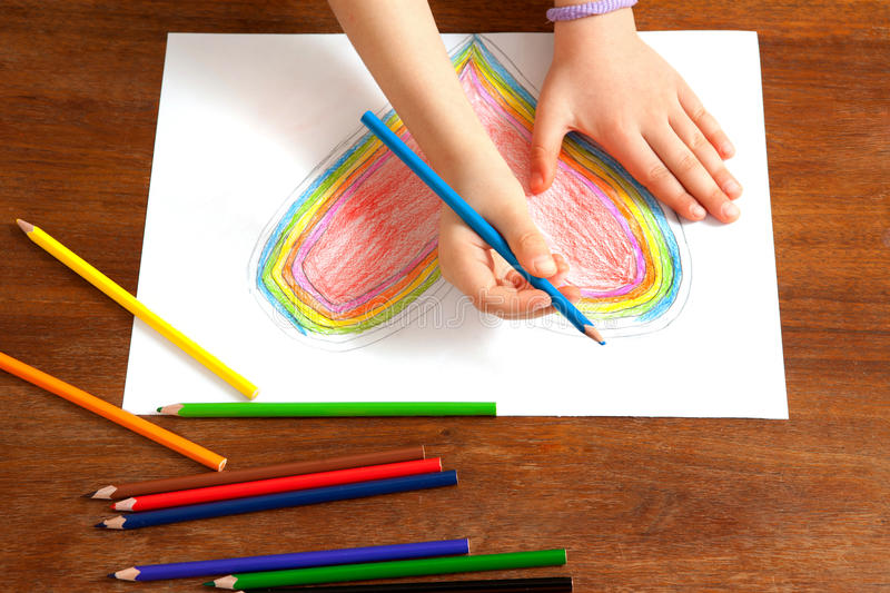 Child's Hands are Drawing a Heart That. Little Girl is Drawing Red Heart. Mothers Day. Fathers Day. Valentines Day. Birthday royalty free stock photo
