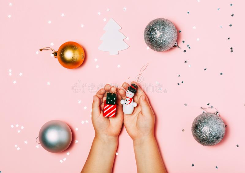 Child`s hands holding big snow flake in hands on sparkling pink background. Bright and festive Christmas and New Year picture. To royalty free stock photos