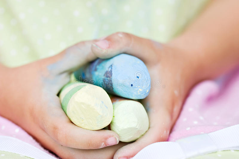 Child's hands holding colored chalk royalty free stock photography