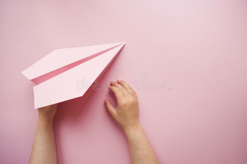 Paper plane in child`s hands. stock photos