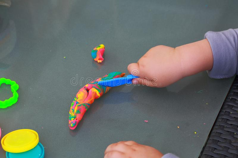 Child`s hands playing with colorful plasticine. Childhood concept. Children background stock image