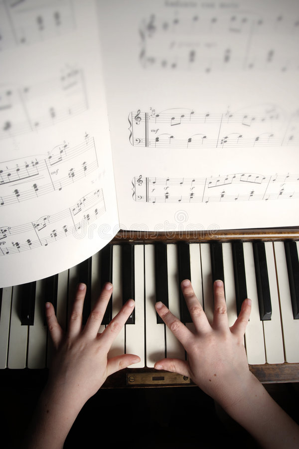 Child's hands playing on a old piano royalty free stock photos