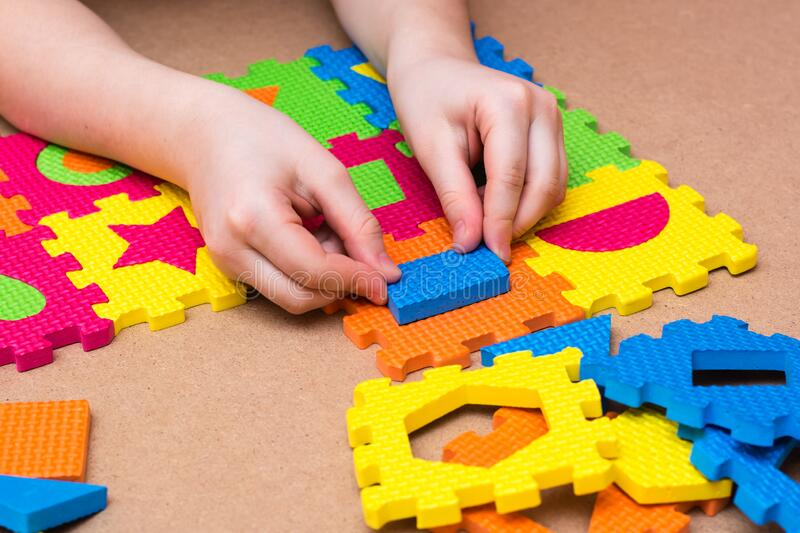The child`s hands put the item in a color puzzle with details of different geometric shapes on the table. Leisure of the child in. Confinement stock photography