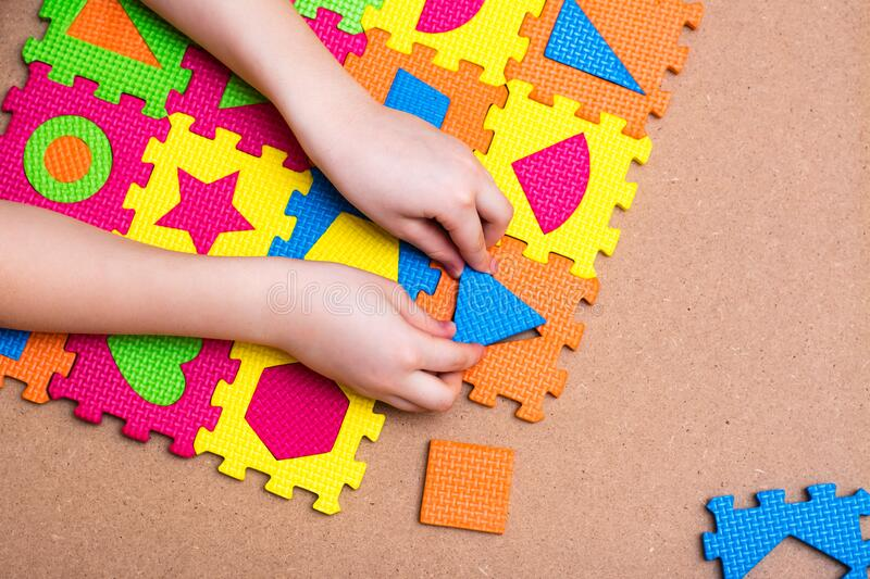 The child`s hands put the item in a color puzzle with details of different geometric shapes on the table. Leisure of the child in confinement. Top view royalty free stock photography