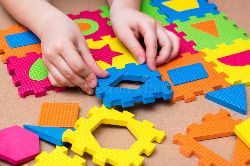 The child`s hands put the item in a color puzzle with details of different geometric shapes on the table. Leisure of the child. In confinement. Table game stock images