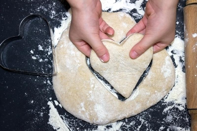 Child`s hands taking a cutted dough heart. Little child preparing dough for backing. A photo from above of Kid`s hands, some flo stock photos
