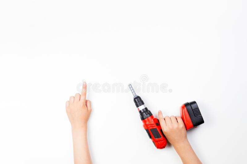Child`s hands on white background. Boy pointing finger up and holding toy drill. Child`s hands on white background. Boy pointing finger up and holding red toy stock photo