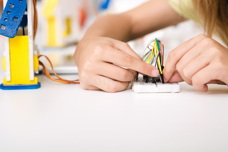 Child`s hands working with wires and circuits. Stem education. Child`s hands working with wires and circuits on robotics project stock photo
