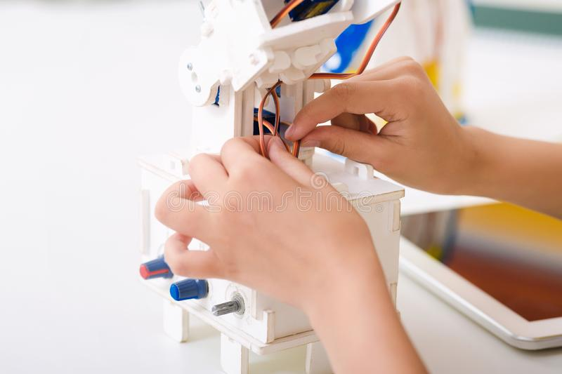 Child`s hands working with wires on his robotics project royalty free stock photo
