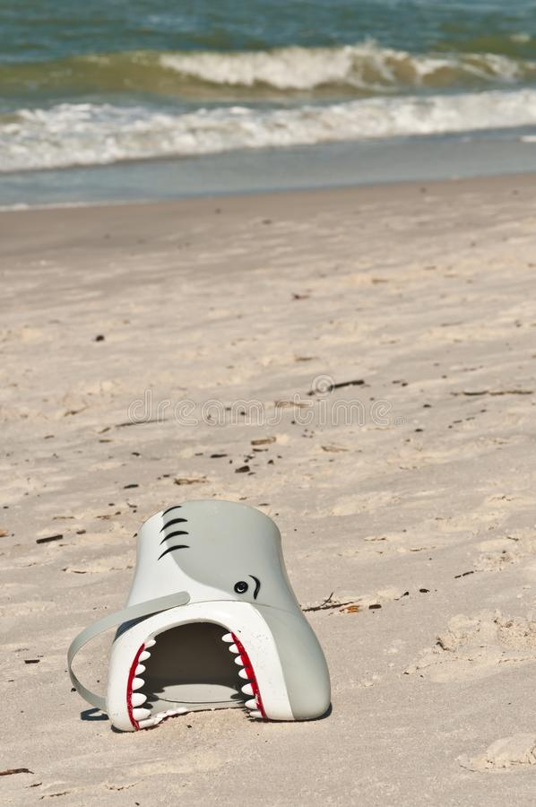 Shark head child`s pail on sandy beach. Child`s head pail laying on a sandy beach with a retreating shoreline on a warm, clear tropical day on the Gulf of Mexico stock photography