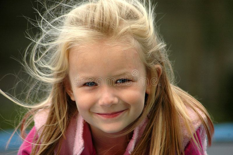 Child natural smile. A beautiful little caucasian white blue eyed girl child with happy expression in her pretty face and her wild long blond hair blowing in the royalty free stock photos
