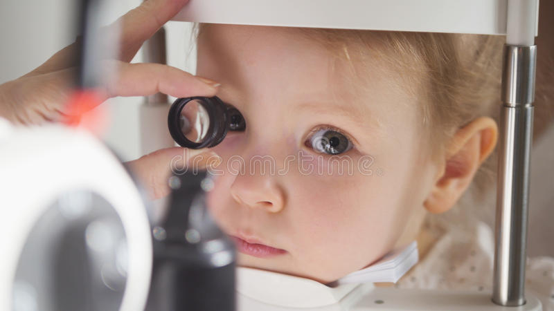 Child`s ophthalmology - doctor optometrist checks eyesight for little girl. Close up royalty free stock image