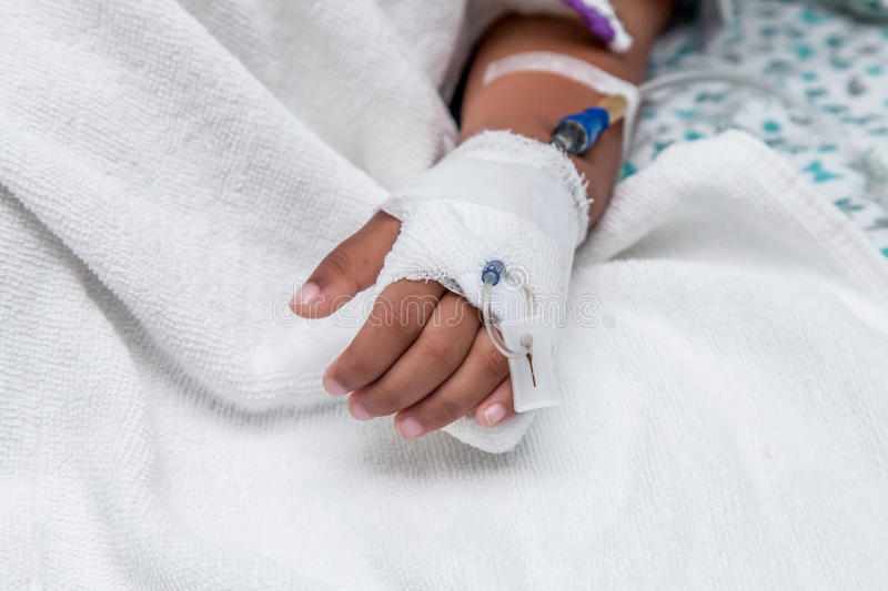 Child's patient hand with saline intravenous (iv) drip royalty free stock photo