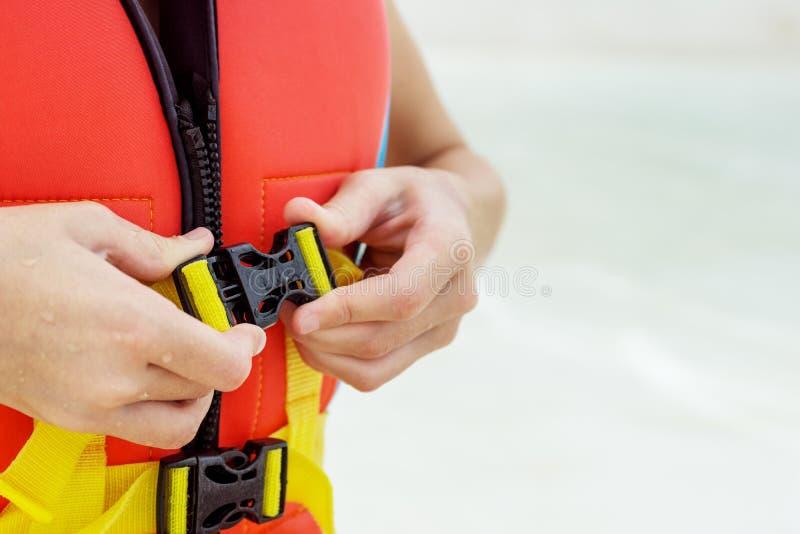Child& x27; s ręki przymocowywają kamizelkę ratunkową Zamazana woda w tle zdjęcia stock