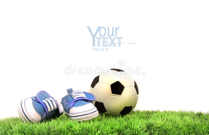 Child's shoes with rubber ball on grass stock images