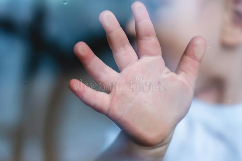Child`s small hand is pressed against the window glass with reflection. Loneliness of children. Orphanage and orphans. The child`s small hand is pressed against royalty free stock photography