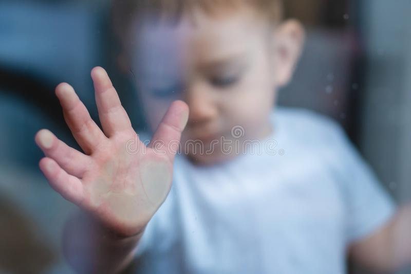Child`s small hand is pressed against the window glass with reflection. Loneliness of children. Orphanage and orphans. The child`s small hand is pressed against stock photos
