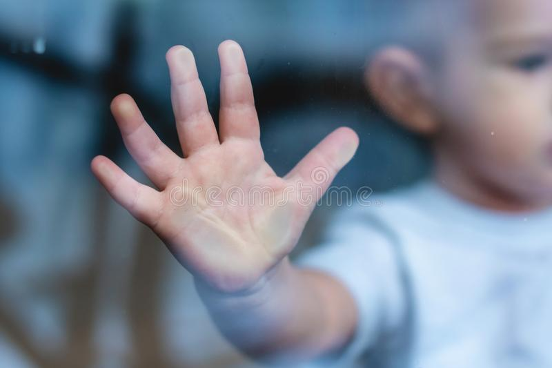 Child`s small hand is pressed against the window glass with reflection. Loneliness of children. Orphanage and orphans. The child`s small hand is pressed against stock images