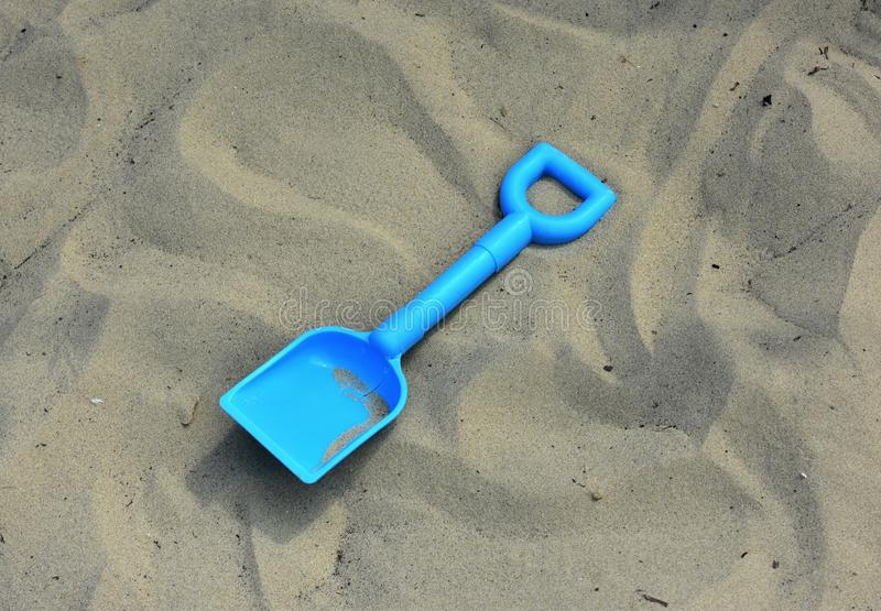 Childs spade / shovel on a sandy beach. Child's spade / shovel on a sandy beach. Childs, bucket, seaside, dicarded, toy, tool, blue, plastic, texture stock photo