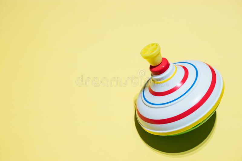 Children`s spinning top Toy.toy spinning top insulation on a yellow background. Kids toys. entertainment for kids stock photo
