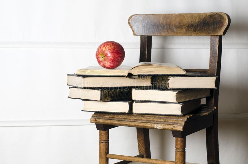 Child's vintage school chair with old books royalty free stock photo