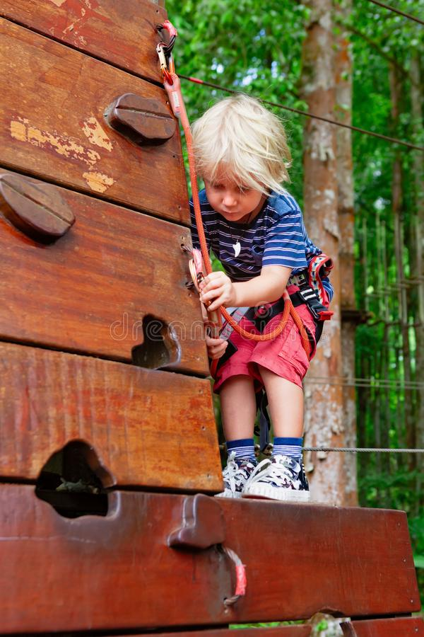 Child in safety harness climb high in adventure rope park stock photo