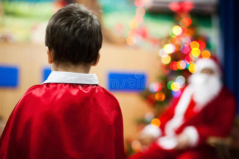 Child and Santa Claus. Wearing a red cloak stock photography