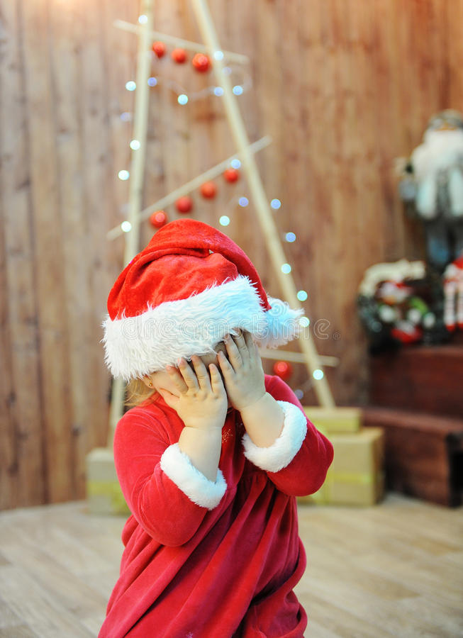 The child in the santa costume closes eyes palms. Christmas decorations in the background stock photo