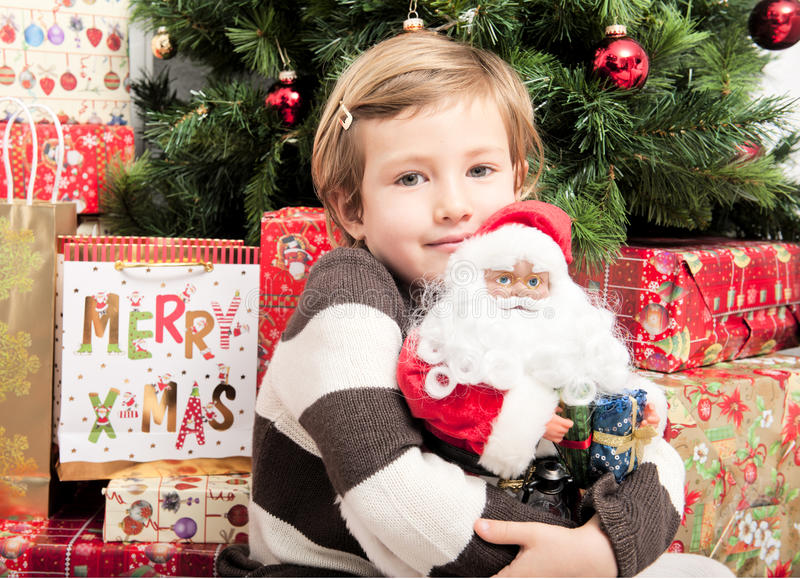Child with santa doll in front of christmas tree. Cute child hugging santa doll in front of christmas tree stock photo