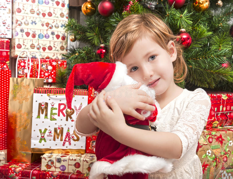 Child with santa doll in front of christmas tree. Cute child hugging santa doll in front of christmas tree stock image