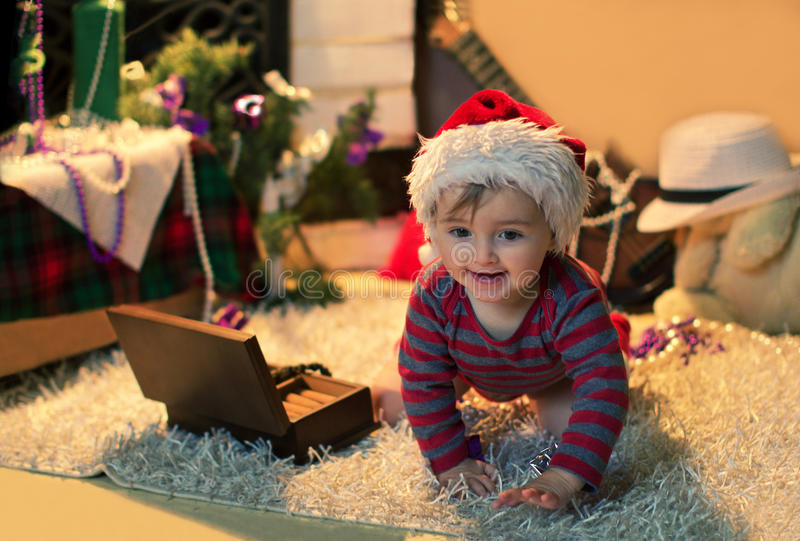 The child in Santa hat crawling on the carpet. Funny baby in Santa hat crawling on the carpet near christmas tree stock photos