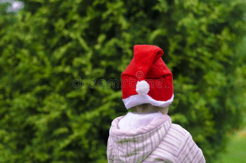 Child in santa hat decorates a christmas tree on the street.  waiting for the  happy new year. stock photography