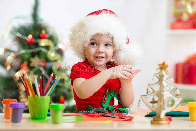 Child in Santa hat making christmas tree of stock image