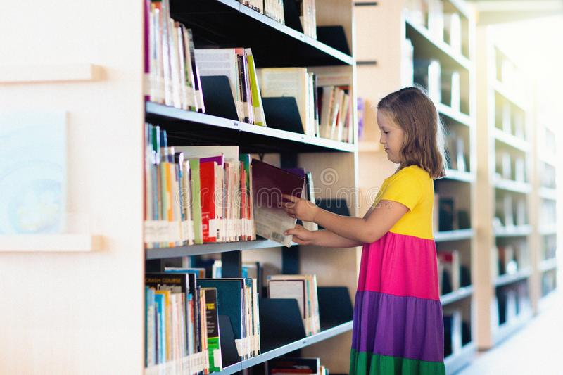 Child in school library. Kids reading books. Child in school library. Kids read books. Little girl and boy reading and studying. Children at book store. Smart stock photos