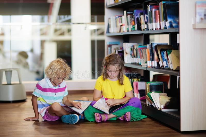 Child in school library. Kids reading books royalty free stock images