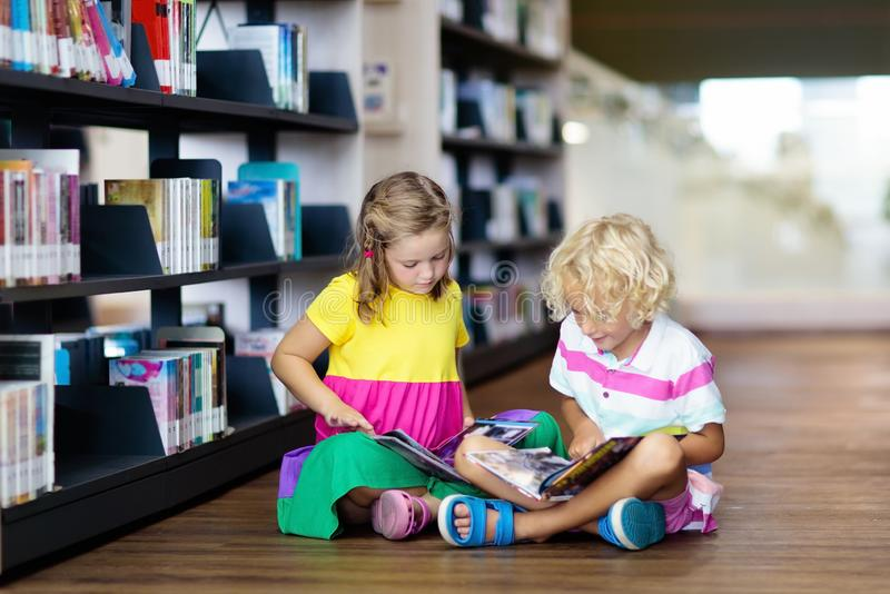 Child in school library. Kids reading books. Child in school library. Kids read books. Little girl and boy reading and studying. Children at book store. Smart royalty free stock images