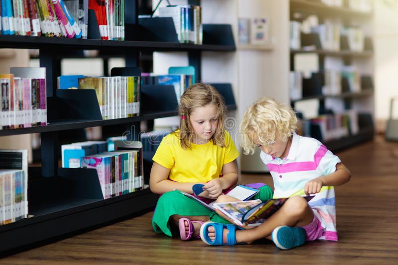 Child in school library. Kids reading books. Child in school library. Kids read books. Little girl and boy reading and studying. Children at book store. Smart royalty free stock photo