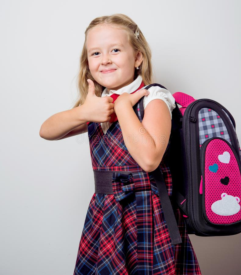 Child in a school uniform. With a backpack royalty free stock photography