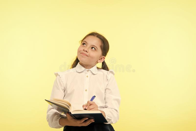Child school uniform kid doing homework. Child girl school uniform clothes hold book and pen. Girl cute write down idea. Notes. Notes to remember. Write essay stock photos