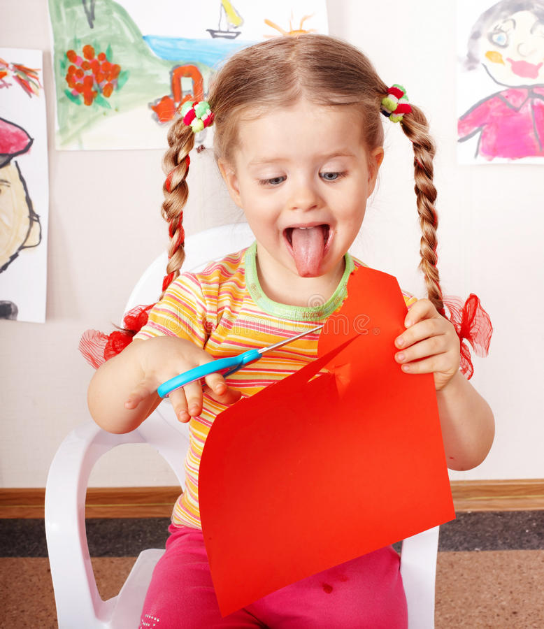 Child with scissors cut paper in play room. Preschool stock photos