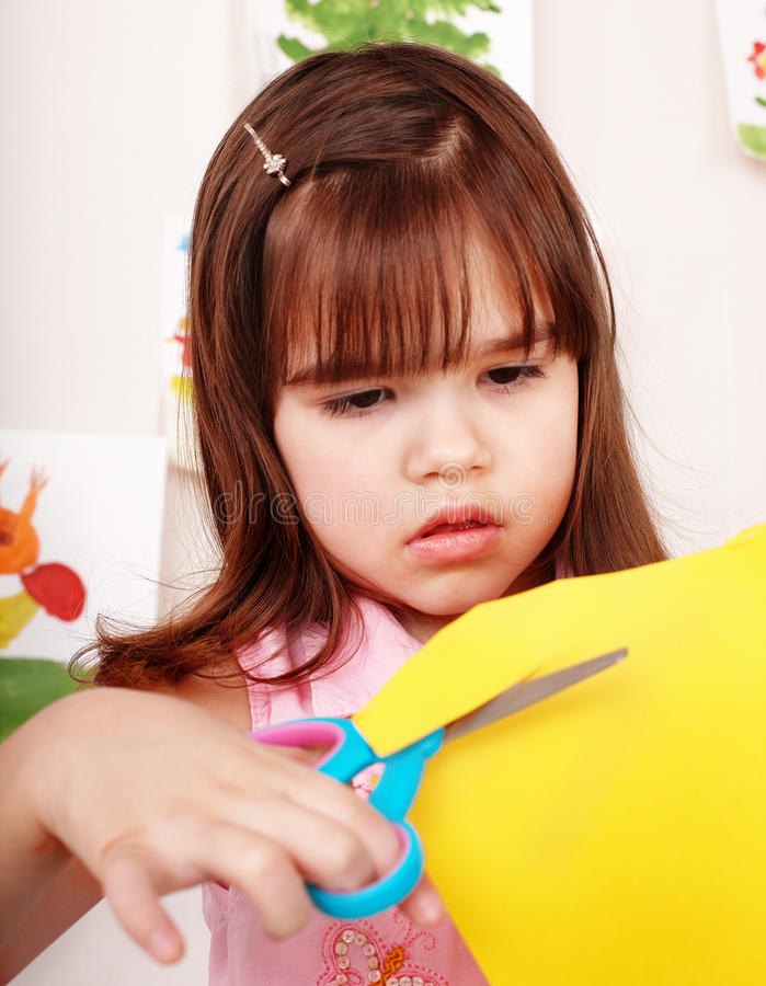 Child with scissors cut paper in play room. stock image