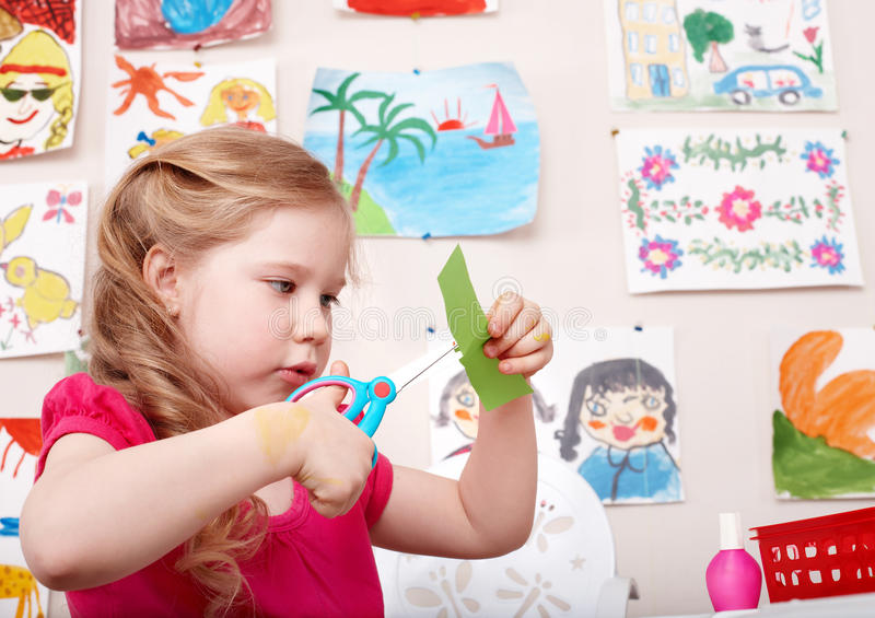 Child with scissors cut paper in play room. Preschool royalty free stock image