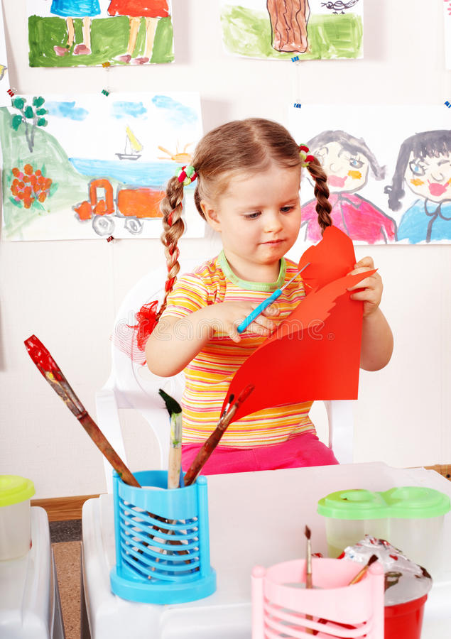 Child with scissors cut paper in playroom. Preschool stock photo