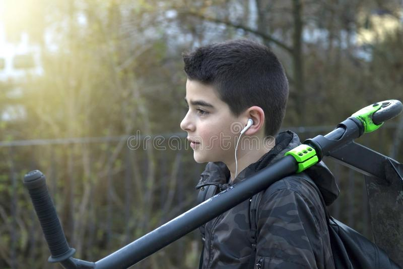 Child with the scooter. While listening to music in the street royalty free stock image