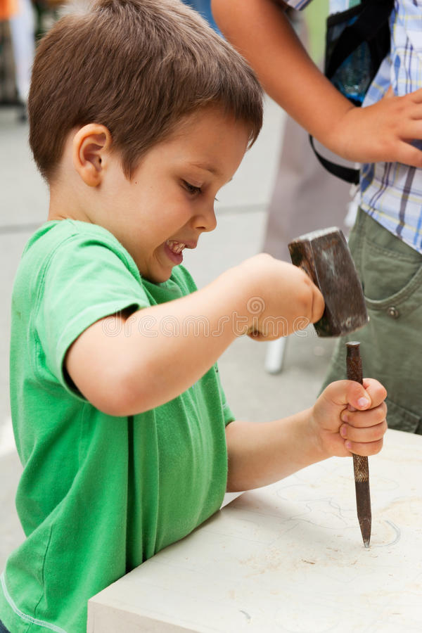 Child sculptor with chisel. And hammer carving rock stock photography