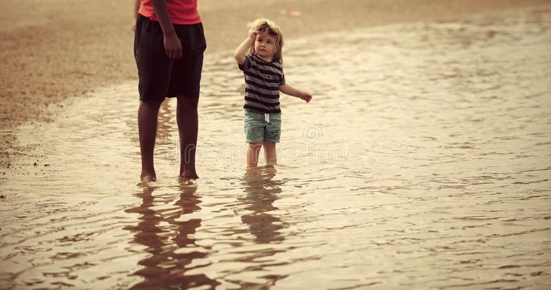 Child at sea. Child under adult supervision walk in water on sea beach stock photo