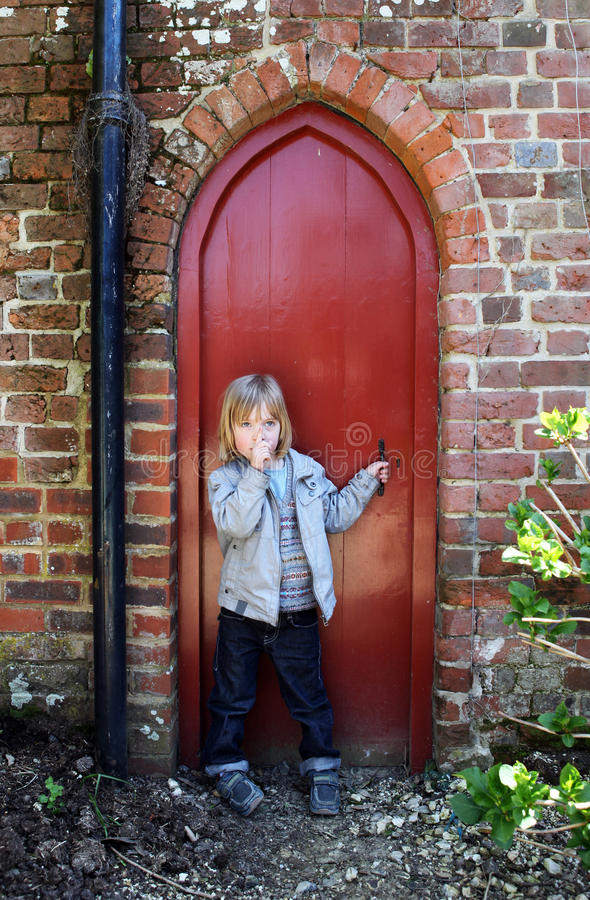 Child secret door. Child by small secret door with finger to lips to sign hush. kid by red wood entrance royalty free stock photography